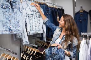girl hanging up denim jackets in store
