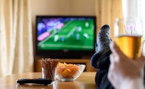 Man with beer watching sports on TV
